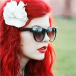 Woman with hair dyed red, wearing shades