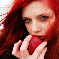 Woman with dyed red hair eating a red apple