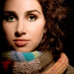 Woman with dark brown curly hair in winter scarf