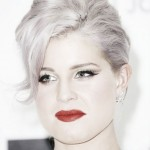 Kelly Osbourne with gray hair, a pale face and red lips