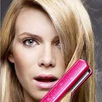 Woman with blonde hair using color lock straightening irons