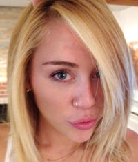Miley Cyrus with blonde hair doing a duck face